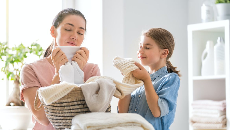 una donna e una bambina che annusano i vestiti lavati da poco con acqua ozonizzata