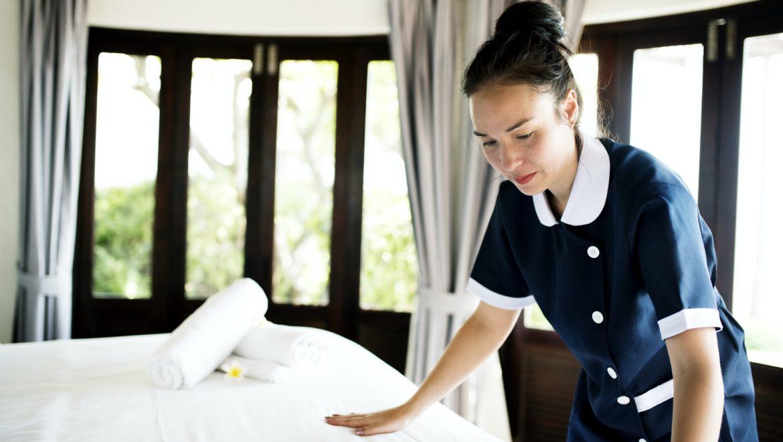 Cameriera che sistema una camera d albergo sanificata con l ozono